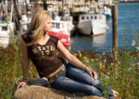 girl with gold belt sitting by boats at portland's waterfront for senior photos