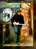 senior boy plays guitar in gritty alley in portland
