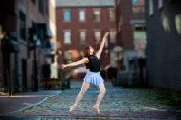 senior girl in blue skirt dances on Portland's wharf street for photo shoot