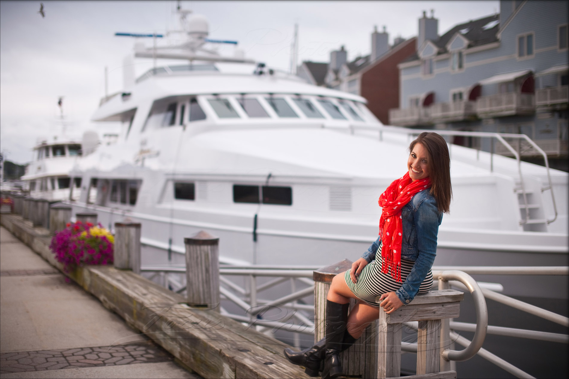 girl in denim jacket and red scarf poses at waterfront for senior pictures in maine