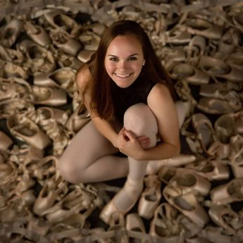 dancer amid hundreds of toe shoes for senior pictures