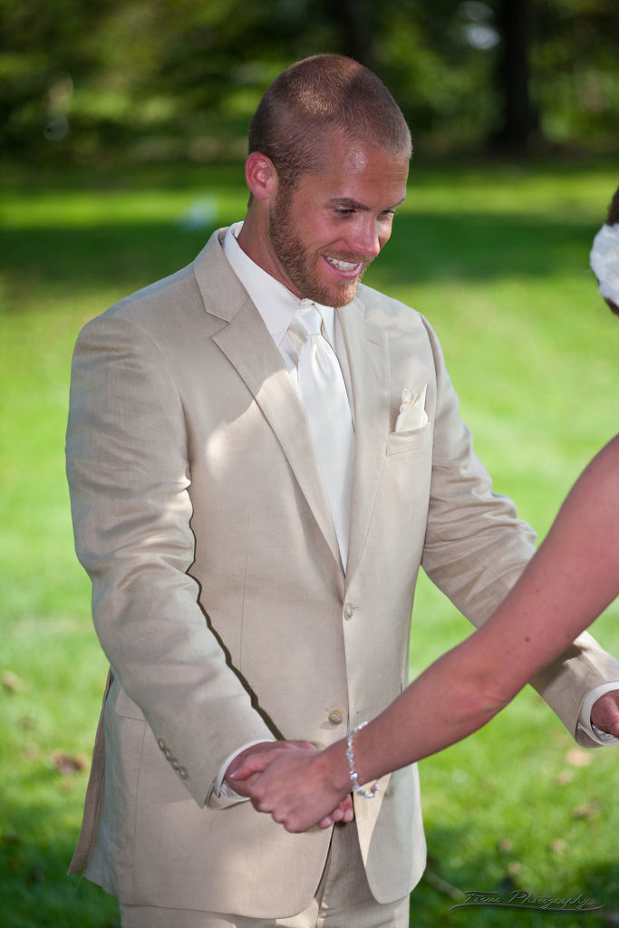 Groom with bride's hands at Maine wedding