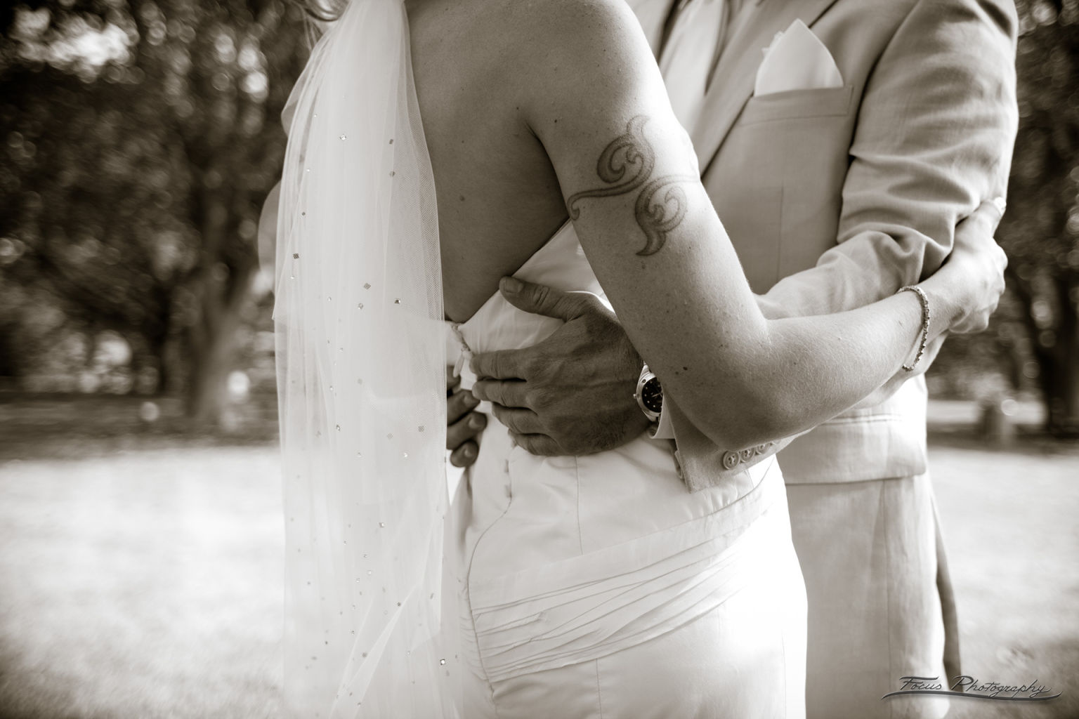 Groom embracing bride with tattoo