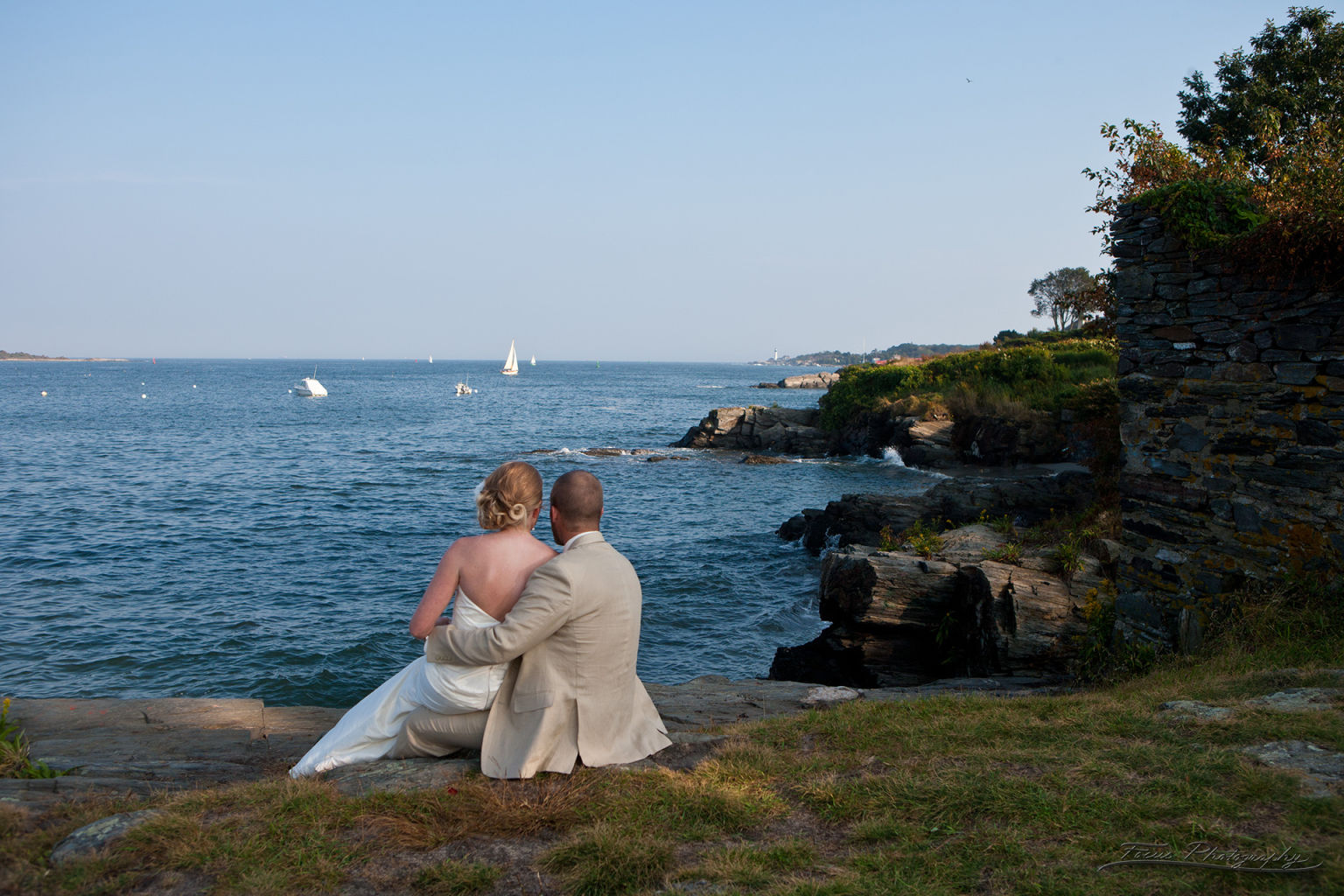 Bride and groom looking out at Maine ocean