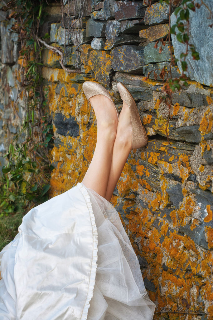 Bride's feet against rocks at Maine wedding