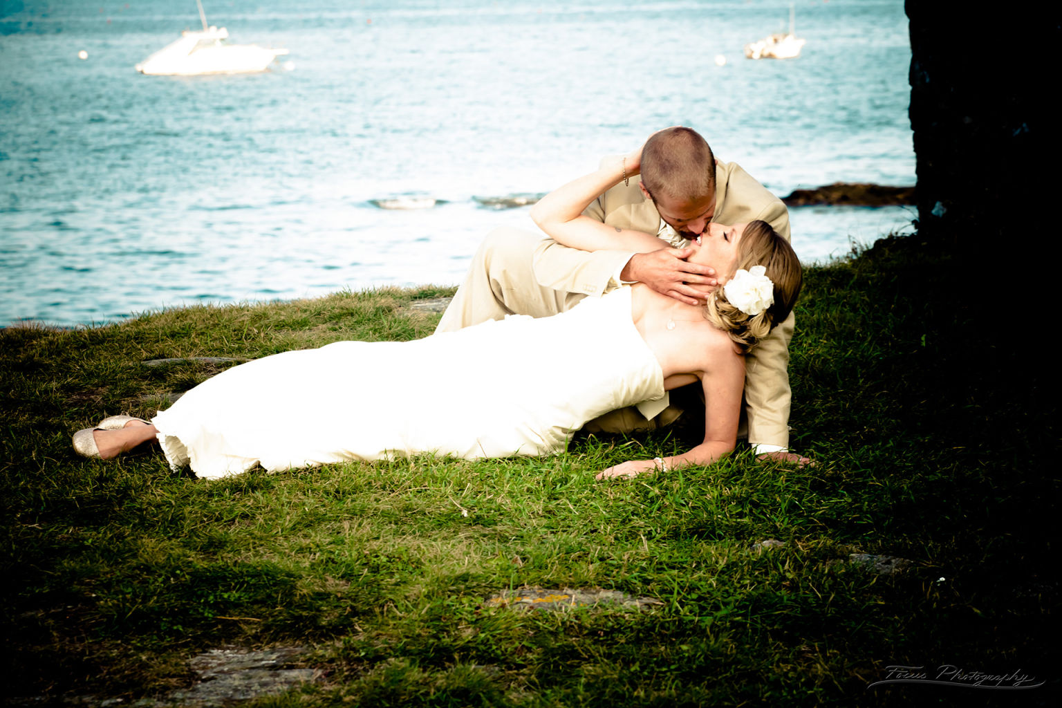 Bride lying down kissing groom at Maine beach