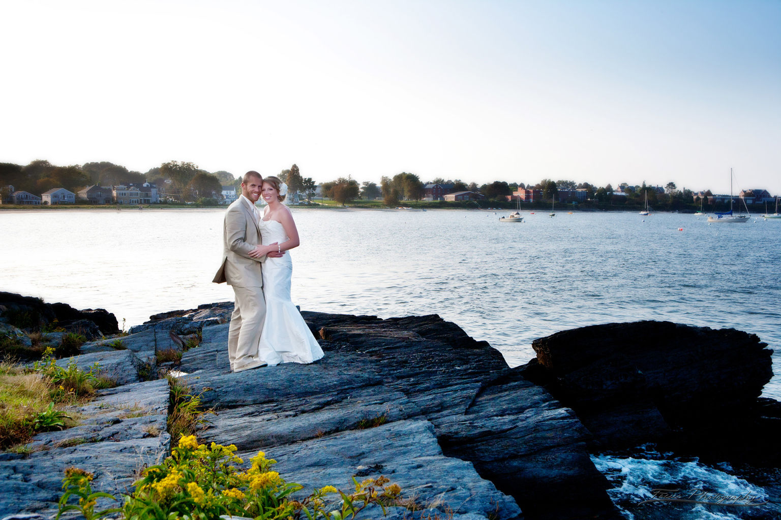 Bride and groom on rocks at Casco Bay Maine