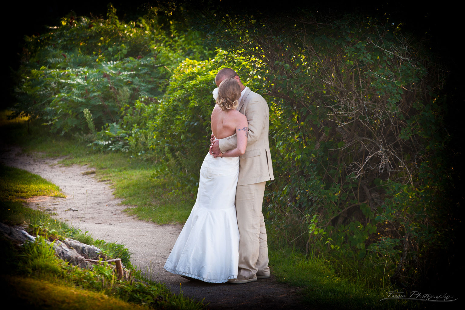 Bride and groom kissing on path in Maine