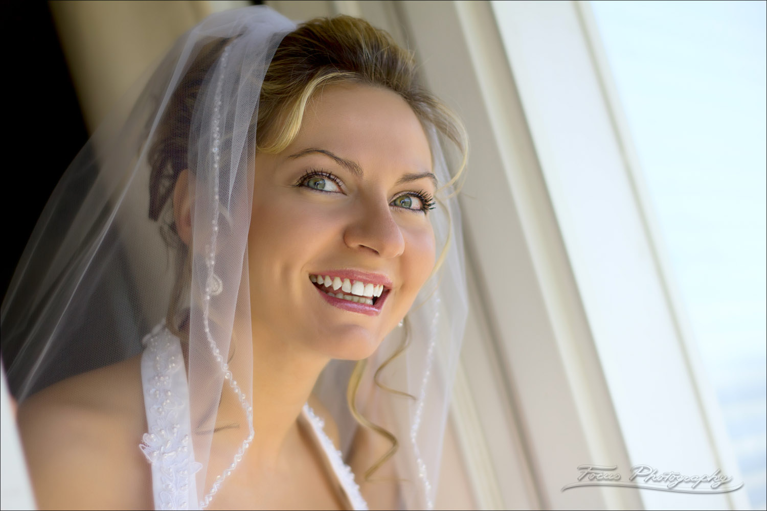 bride looks out window on wedding day