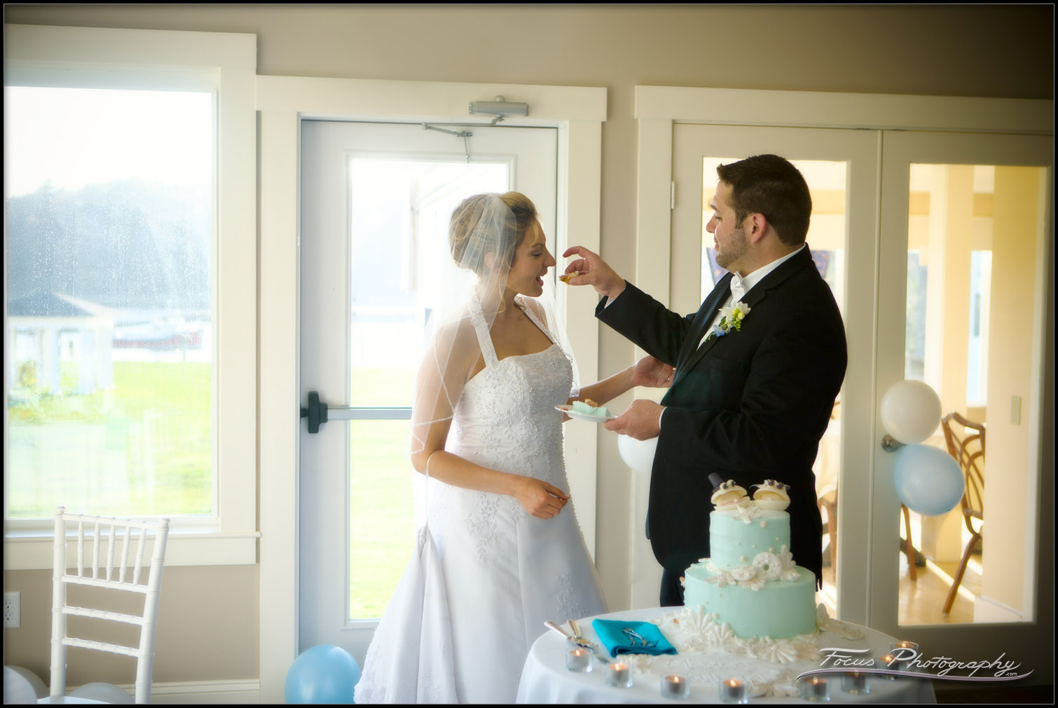 The groom feeds the bride during cake cutting at Nonantum resort