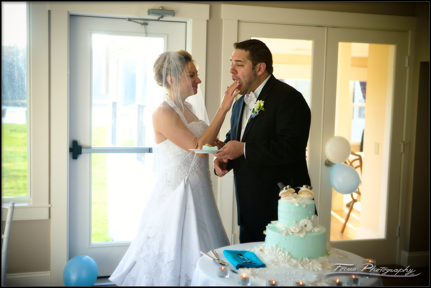 The bride feeds the groom at Maine wedding in Kennebunkport