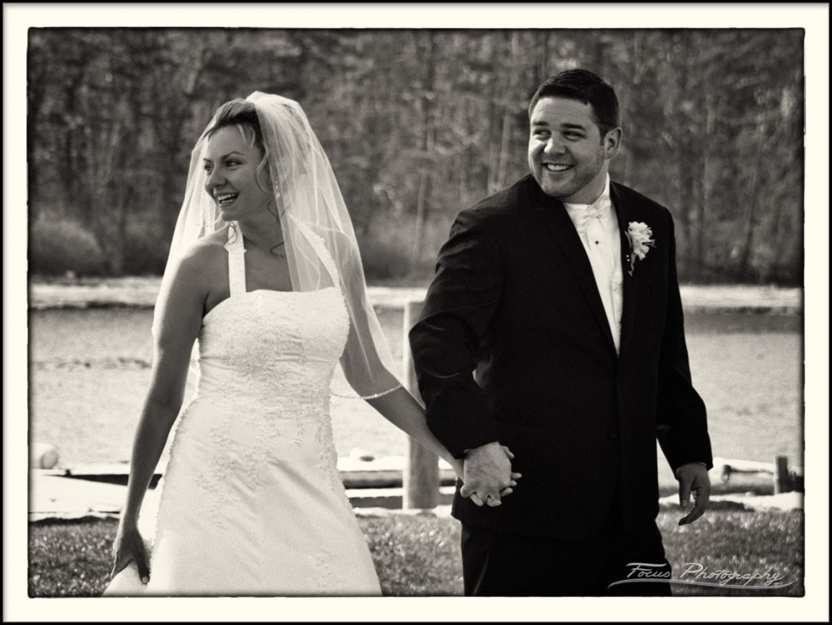 The bride and groom laughing after their wedding ceremony at the Nonantum Resort in Maine. Wedding Photography by Focus