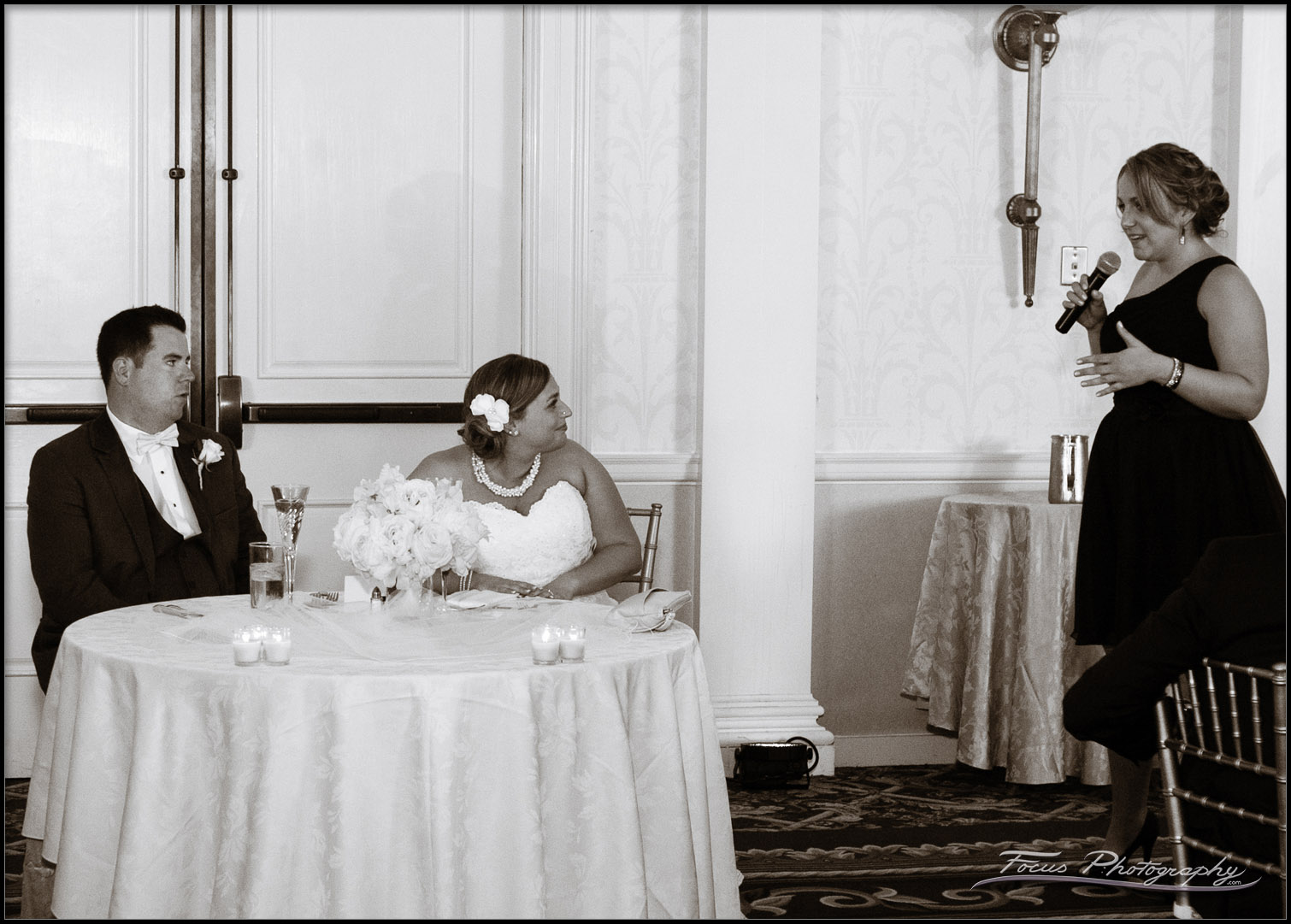Black and White image of toast being given by Maid of Honor