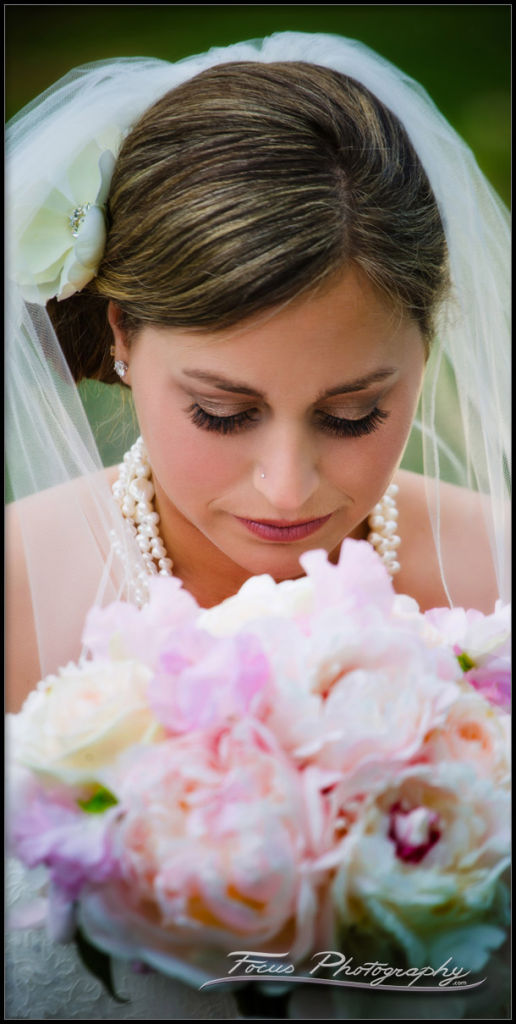 Beautiful bride admires her bridal bouquet