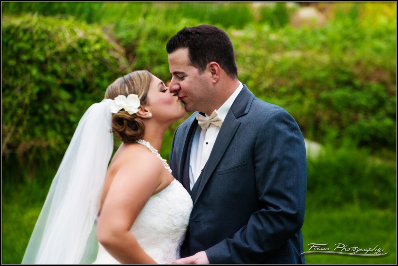 a kiss during wedding photos