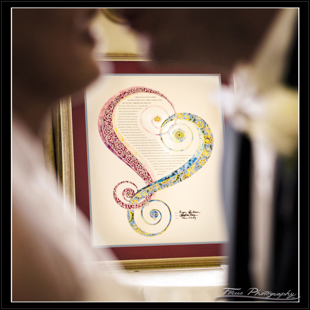 Ketubah (Jewish wedding contract) behind bride and groom at Wentworth wedding - photography by Focus