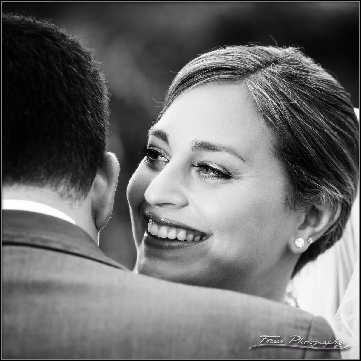 Bride smiles over Grooms shoulder