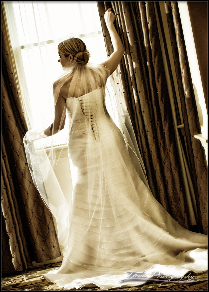 The wedding gown from the back, as the bride looks out the window