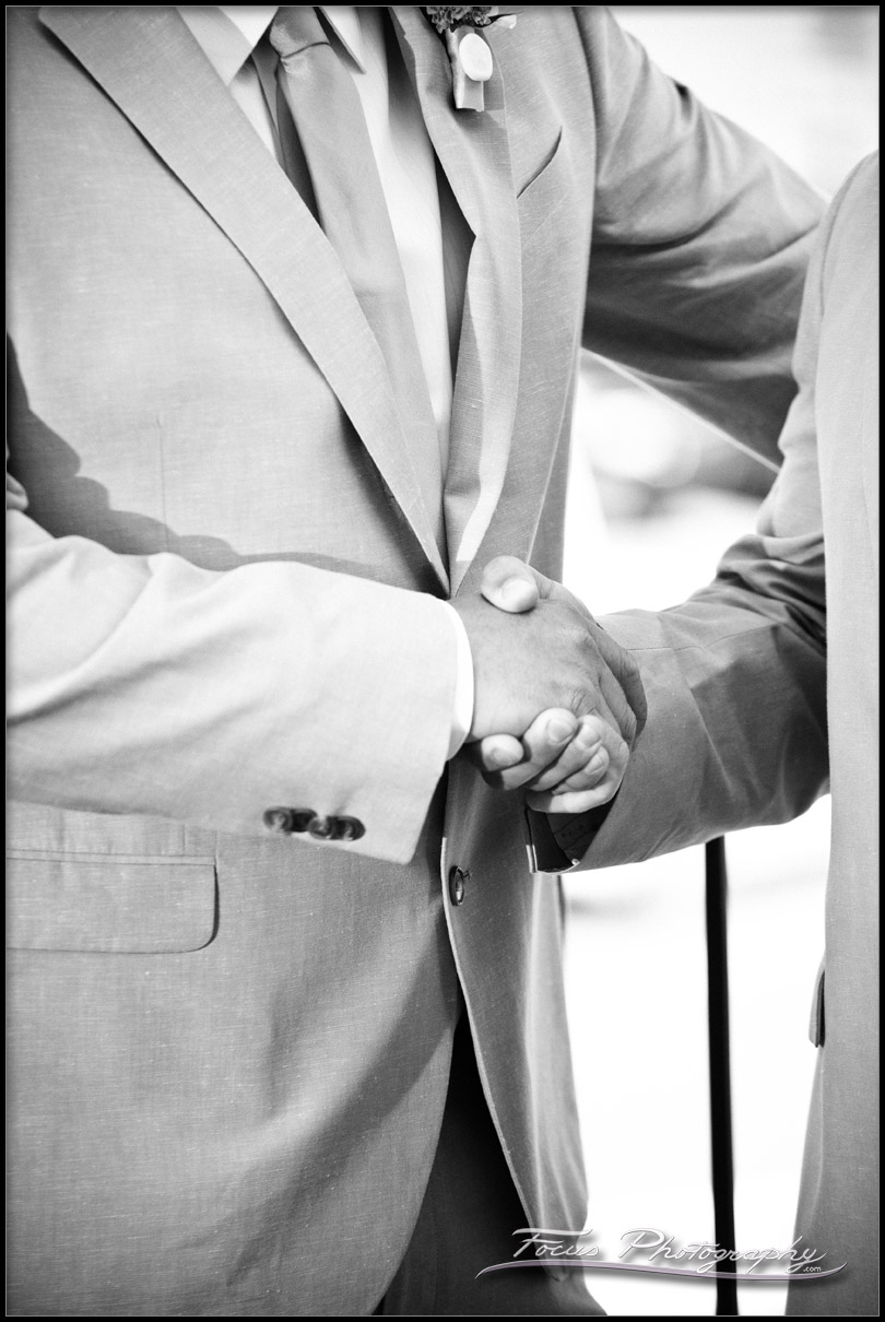 The best man shakes the groom's hand