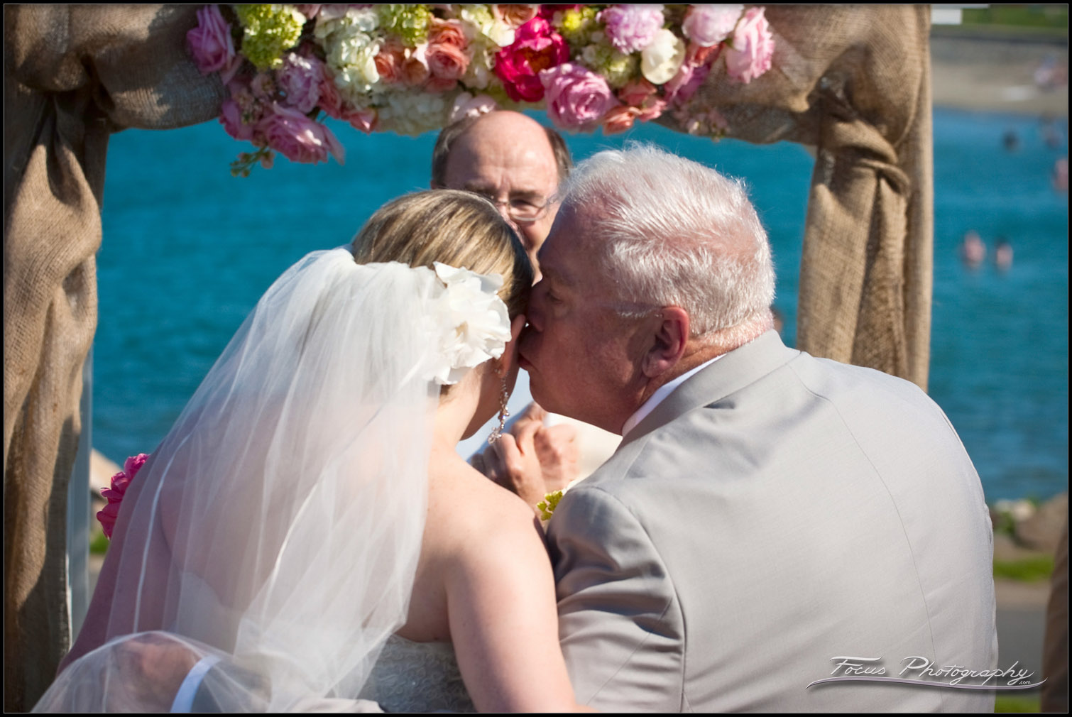 the father of the bride gives her a kiss as he leaves her at the wedding altar