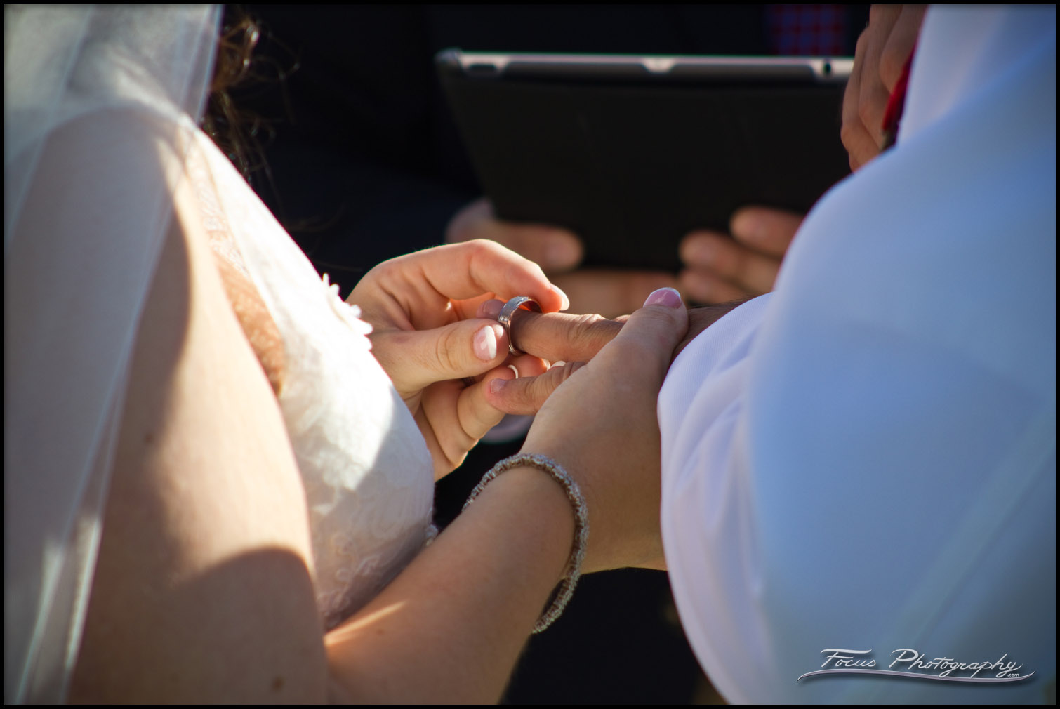 Bride places the grooms ring on his finger during