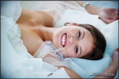 a happy portrait of a bride laying on the ground