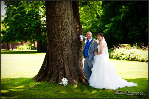 the bride and groom leaning against a tree