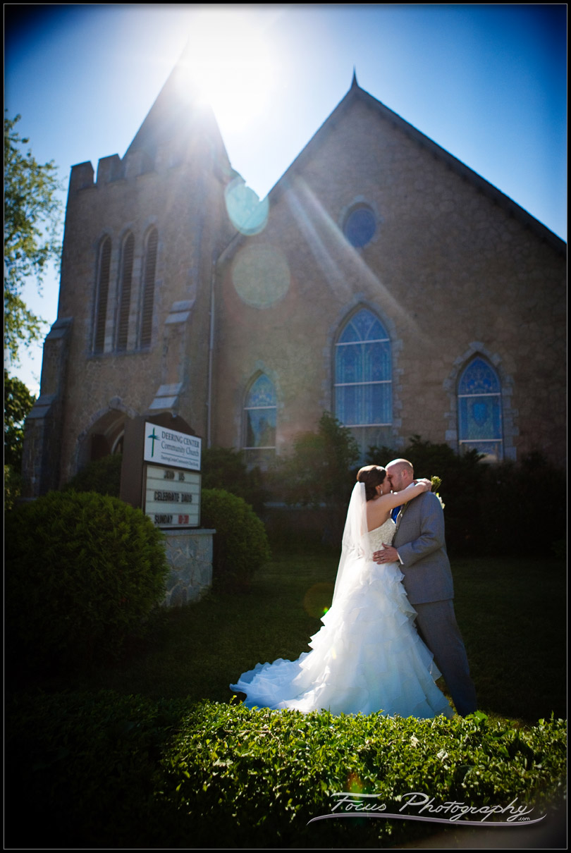 Bride and groom in the sunlight outside Deering community church at Maine wedding - photography by Focus