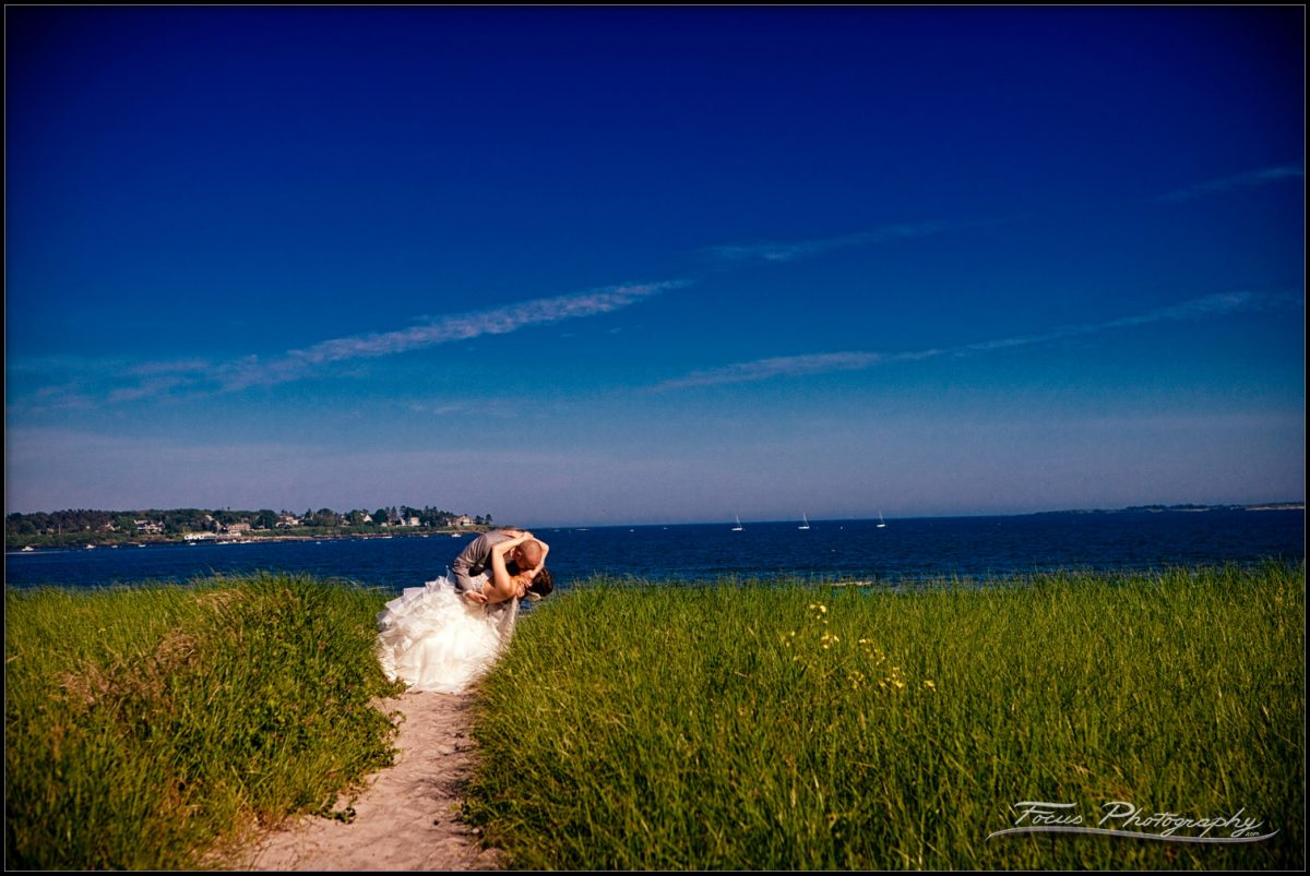 wedding couple dips in the dunegrass of Pine Point Beach in Scarborough, Maine