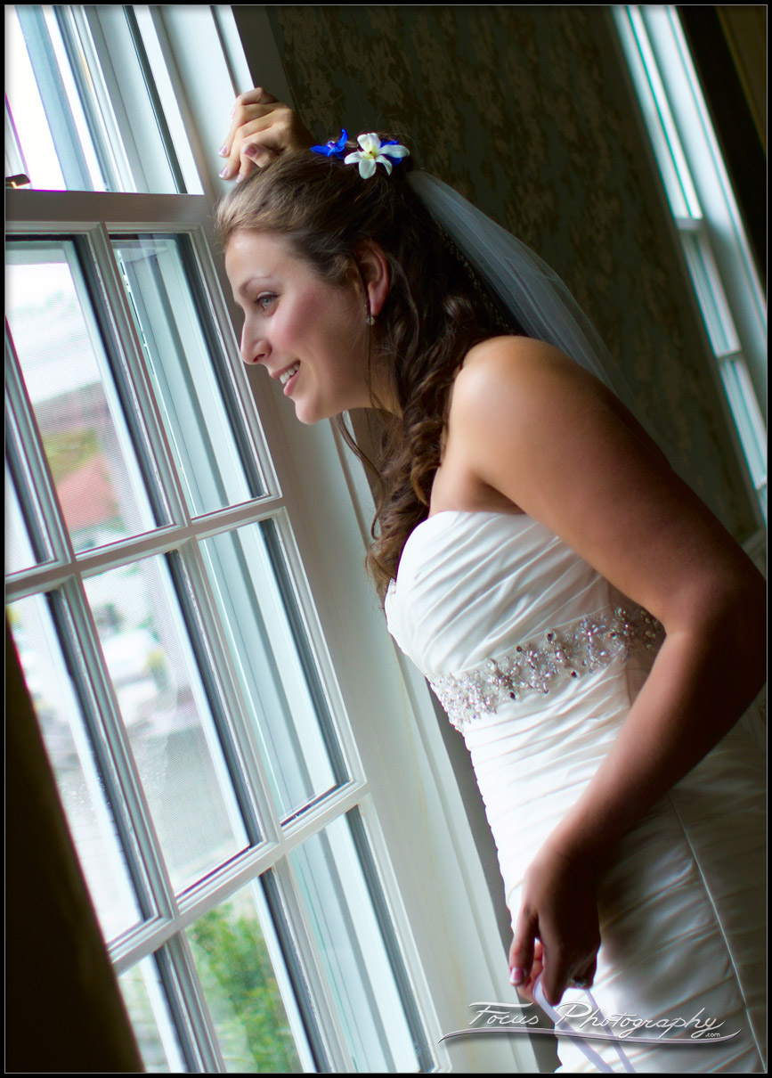 bride looks out window at Colony Hotel Wedding