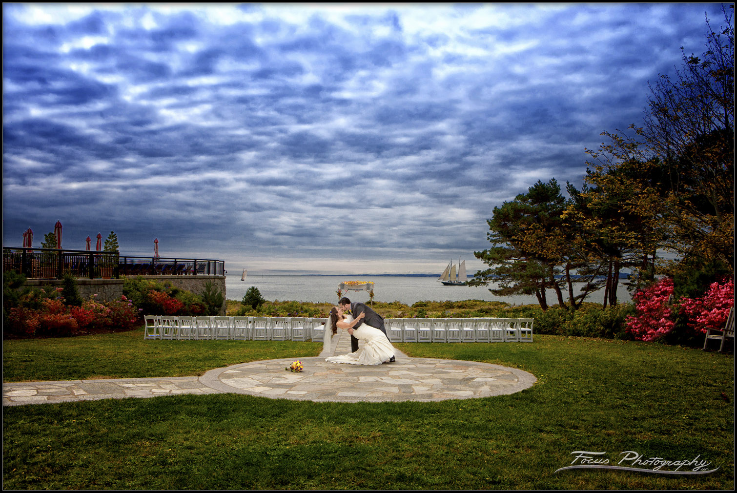 Wedding couple kiss at Colony Hotel in Maine - great sky and fall color