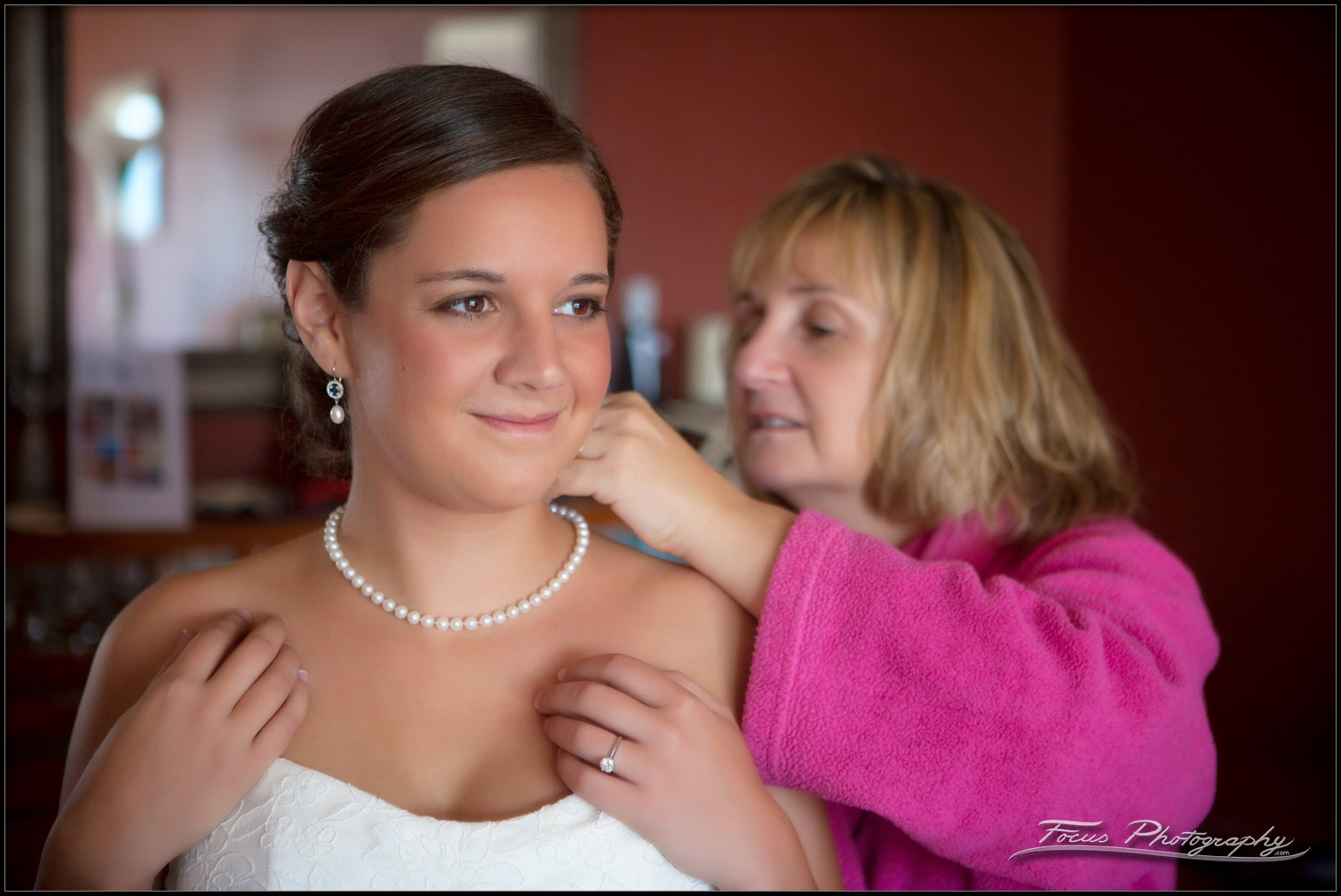mother puts pearls on daughter