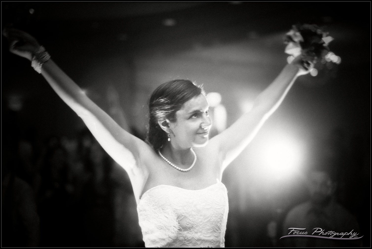 bride holds flowers in victory stance