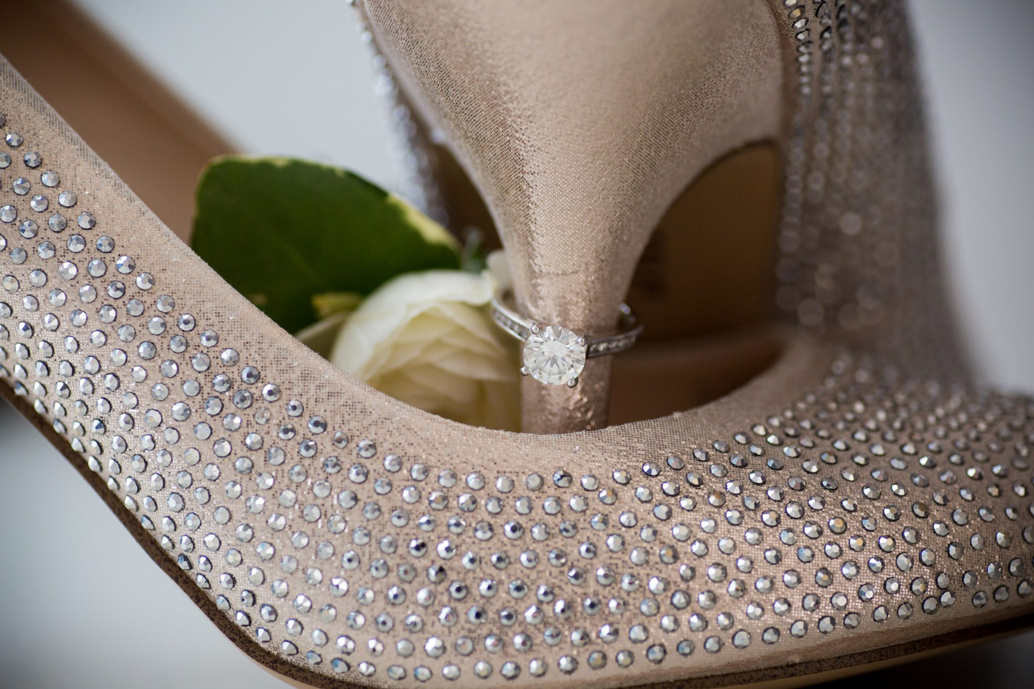 Engagement solitaire on bride's wedding shoes