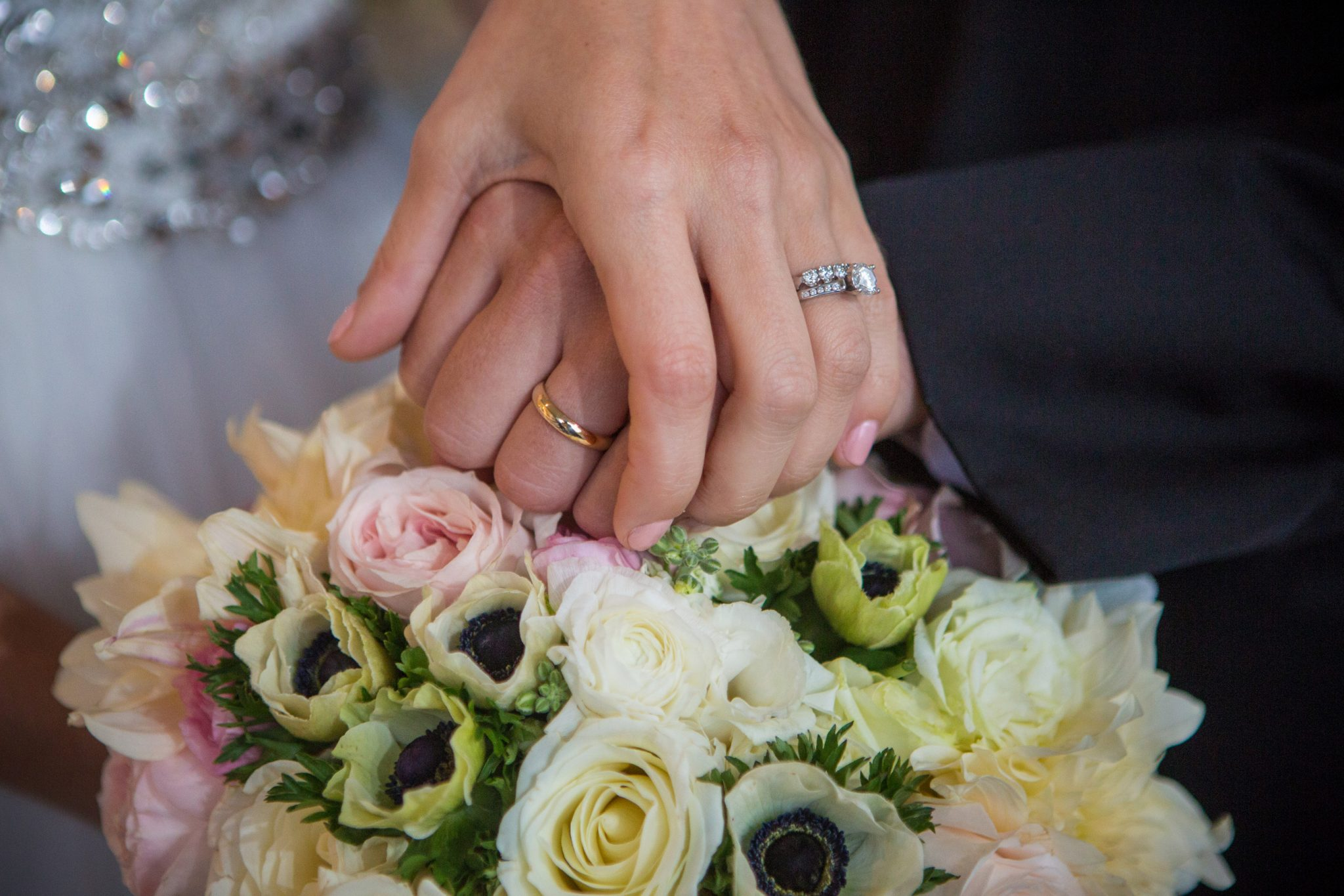 wedding rings on hands above flower bouquet by Laurie Andrews