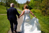 The bride and groom walk down a path at the Eastern Prom.