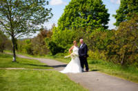 Full-length portrait of bride and groom with trees in background.