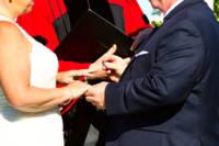 Ring exchange - groom puts wedding band on bride's finger.