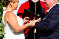 Ring exchange - bride puts wedding ring on groom's finger.