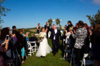 Bride and groom raise hands in the air after being married.
