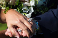 Hands and wedding rings by flowers.