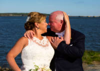 Bride and groom kiss with casco bay in background.