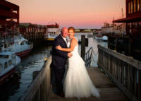 Bride and groom at sunset with Casco Bay in background.
