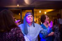 Man on dance floor with tie around his head.