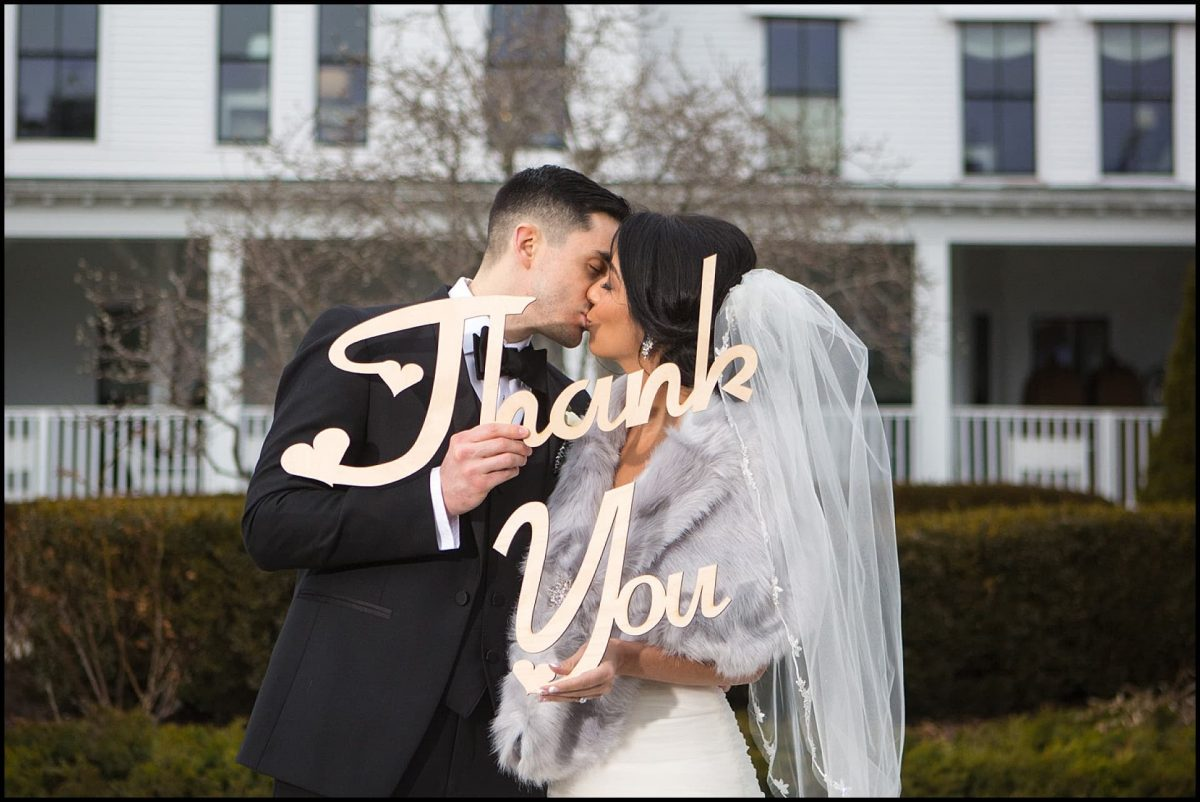 couple kisses behind thank you sign