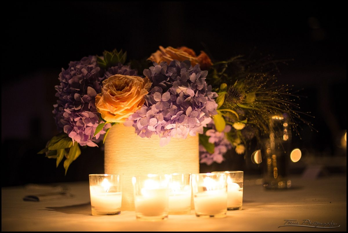 flowers illuminated by candles at wedding