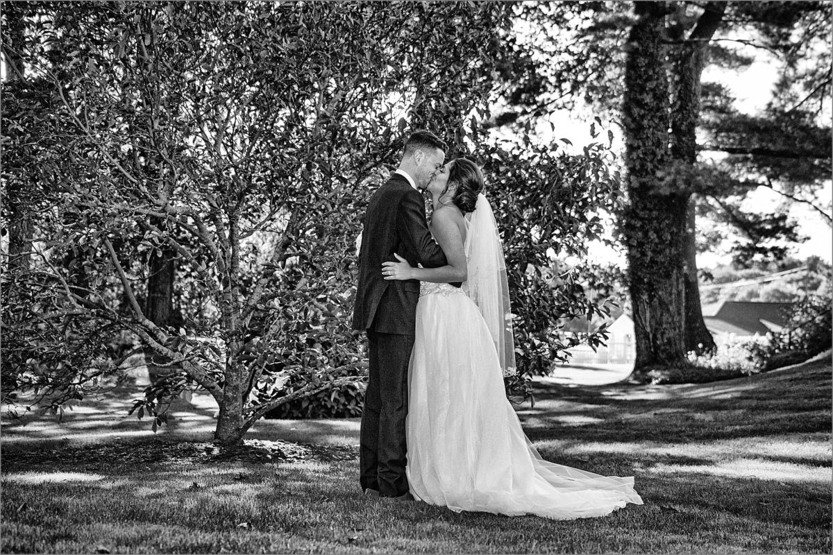 black and white kiss photo in gardens