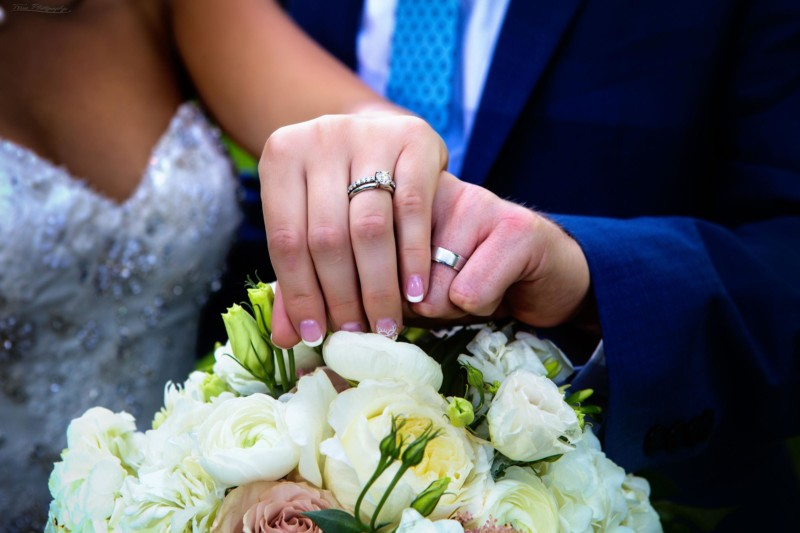 wedding rings on couple above flowers