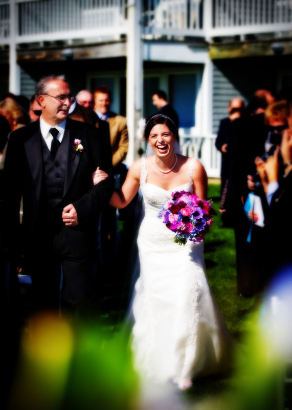 Christa laughing down the aisle with her father