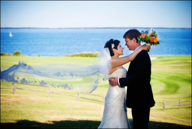 bride and groom with veil blowing in breeze